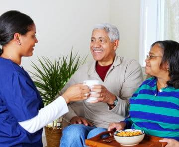 caregiver serving tea to couple senior