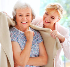 caregiver giving a towel to old woman