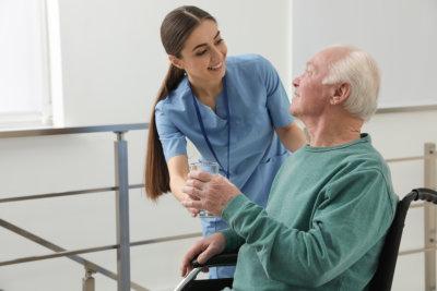 Nurse giving water to senior men in wheelchair at hospital