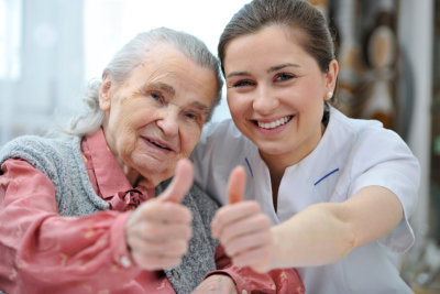 Caregiver with her senior female patient doing thumbs up
