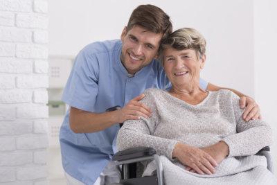 Male nurse hugging his senior women patient sitting on a wheelchair