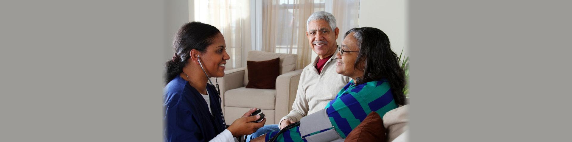 caretaker checking blood pressure on a senior